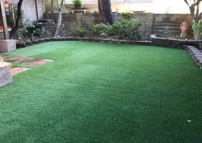 backyard landscape with artificial turf and stone boarder garden