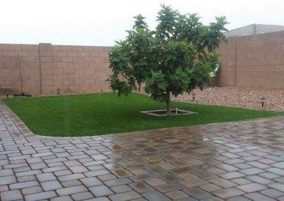 brick and artifical turf back yard